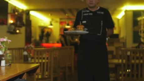 Hamburger being served in restaurant