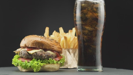 Hamburger with fries and a soda on a dark background