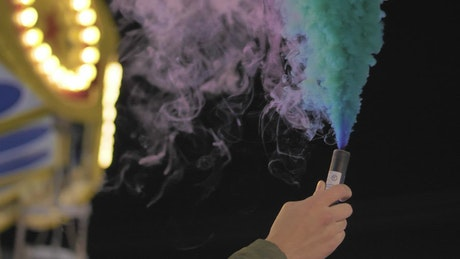 Hand holding a multicolored smoke bomb at the fair