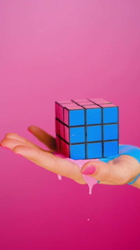 Hand holding a rubik cube that seems to melt on a pink background