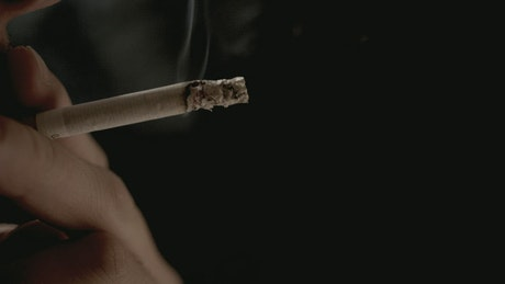 Hand holding cigarette with exhaled smoke on black background