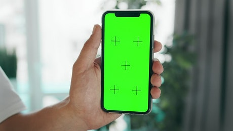 Hand holding mobile phone with greenscreen