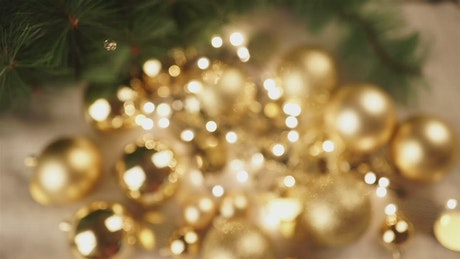 Hand holds out Christmas ornament with gold bokeh background