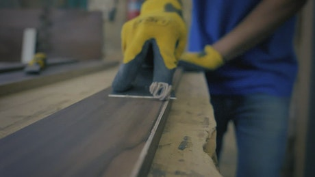 Hand of a carpenter leveling a wooden board