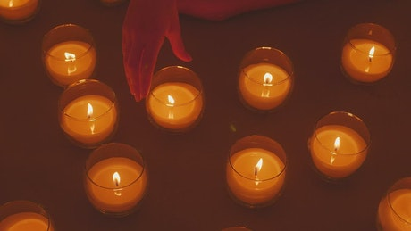 Hand of a lady arranging burning candles