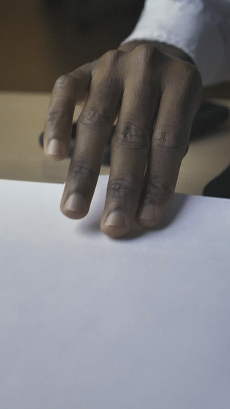 Hand of a man on a desk taking a sheet of paper