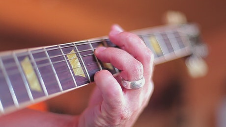 Hand of a man playing chords on a guitar