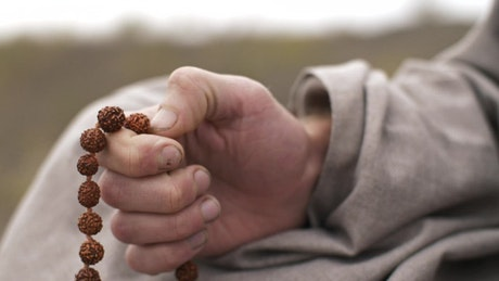 Hand of a man praying with beads