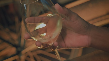 Hand of a man shaking champagne from a glass
