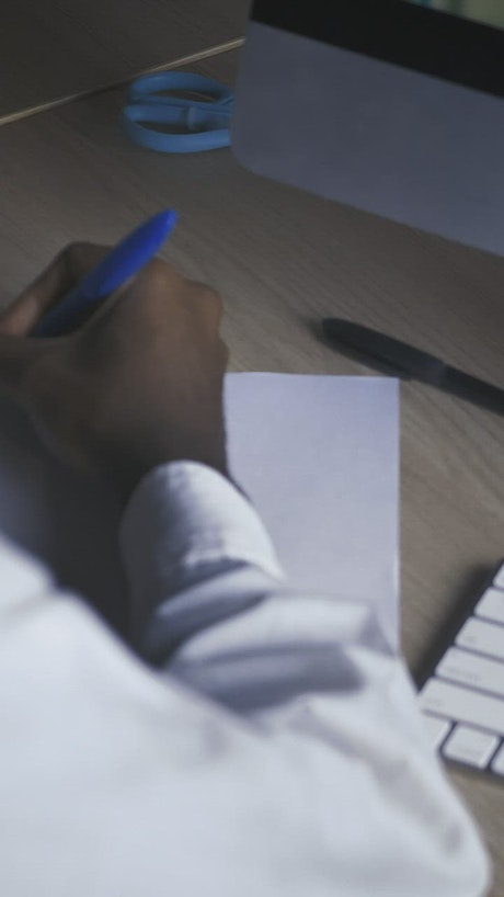 Hand of a man writing on a sheet on a desk