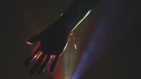 Hand of a person in the dark through colored lights