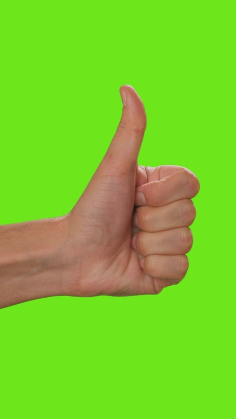 Hand of a person raising the thumb on a green background