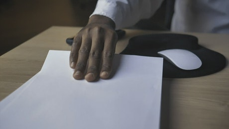 Hand of a person taking a blank sheet of paper