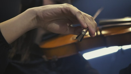 Hand of a violinist gently playing her instrument