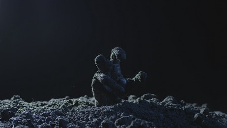 Hand of a zombie coming out of his grave at night