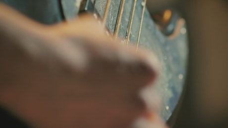 Hand playing an electric guitar