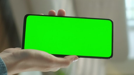 Hand showing a cellphone with a chroma key screen