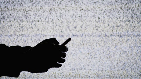 Hand texting with TV static in the background