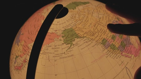 Hand turning a luminous earth globe in the dark