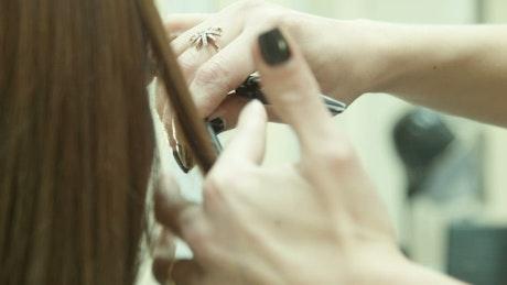 Hands cutting long hair