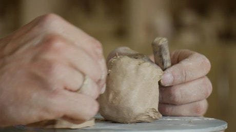 Hands cutting the clay with a wire