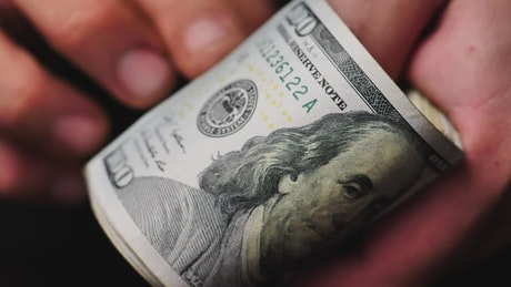 Hands flipping through a wad of dollars seen very close