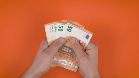 Hands full of money on an orange background