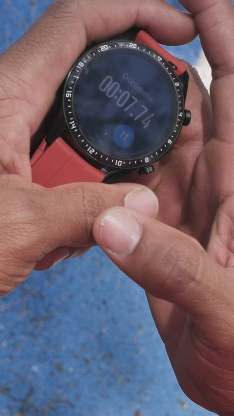 Hands holding a smart watch with the stopwatch running