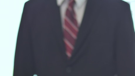 Hands in a handshake with a person in a suit in the background