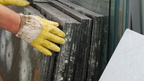 Hands in yellow gloves touching glass sheets