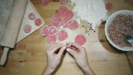 Hands making red dumplings on the table