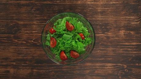 Hands mixing a lettuce salad