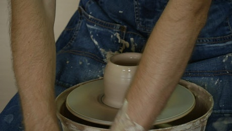 Hands molding wet clay spinning