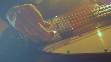 Hands of a bass player playing a song