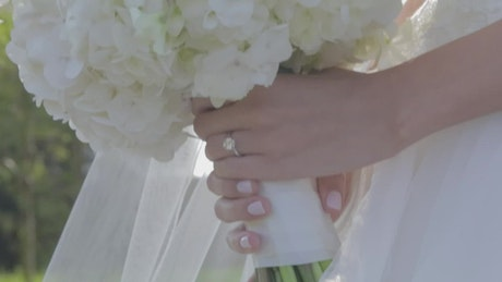 Hands of a bride with the ring and her bouquet