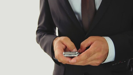 Hands of a businessman texting on a cell phone