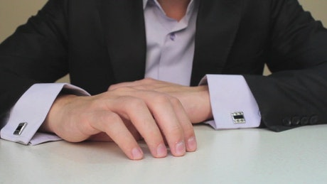 Hands of a man in a suit doing a waiting gesture