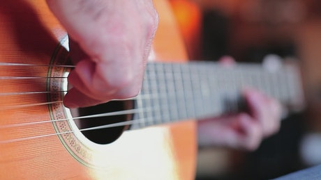 Hands of a man playing the guitar