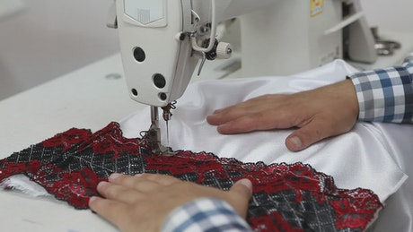 Hands of a man sewing on a machine