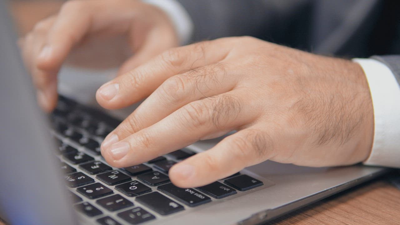 Hands of a man typing on a laptop