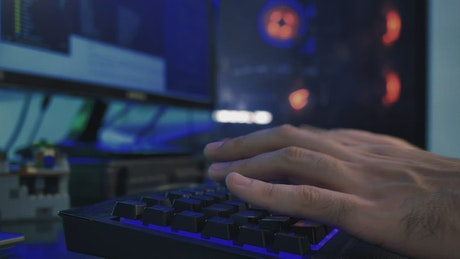 Hands of a programmer working on his computer