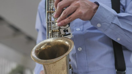Hands of a saxophonist playing a song