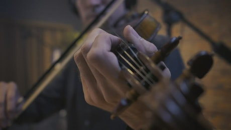 hands of a skilled violinist playing a piece