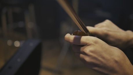 Hands of a violinist putting pitch to her violin bow