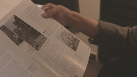 Hands of a woman slowly leafing through a magazine