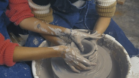 Hands of two girlfriends shaping a vase with clay