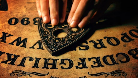 Hands playing Ouija board