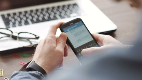 Hands scroll through Facebook on mobile at desk