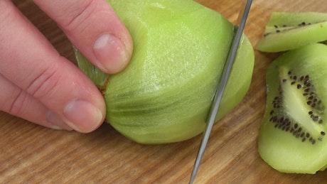 Hands slicing a kiwi