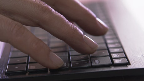 Hands typing on a flat keyboard